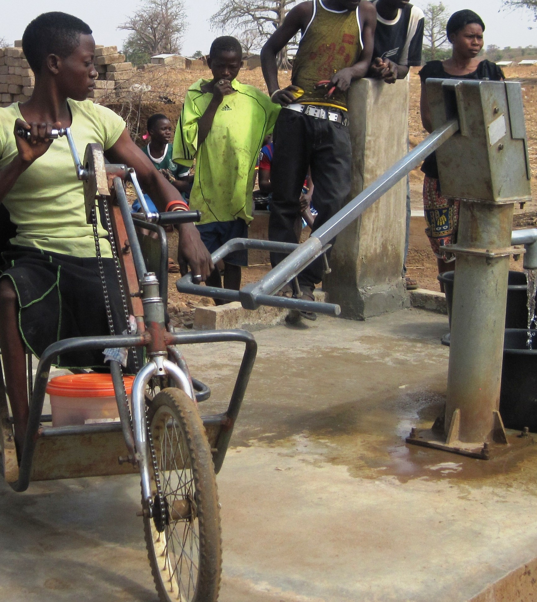 A woman using a tricycle operates a lengthened pump handle