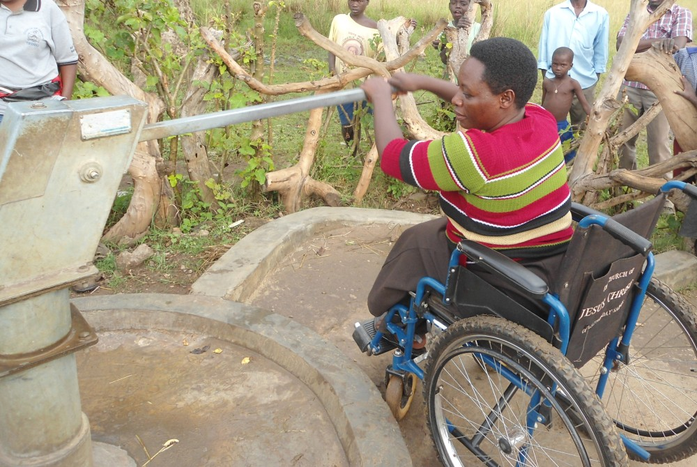 A woman using a wheelchair is operating a handpump from a concrete apron