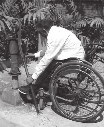 A man using a wheelchair is handling a handpump placed at 90 degrees to the height of the wheelchair
