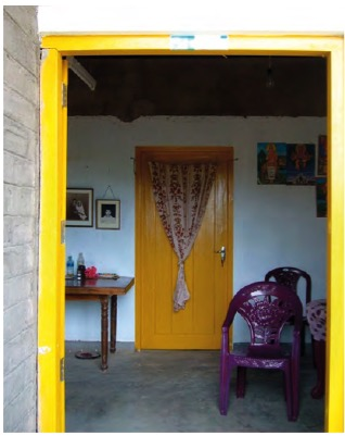 Doorway to a room, where the door frame is painted yellow