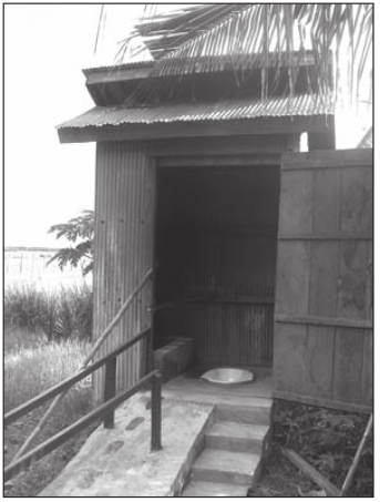 Toilet with a ramp made of concrete, which has footsteps painted on it. Next to the ramp is a stair.