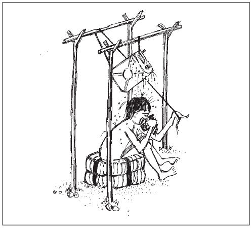 A boy sitting on two tyres, using a shower system where a jerrycan has been hanged across 4 poles and managed through a rope
