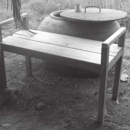 A bathing bench in wood in front of a jar of water for washing
