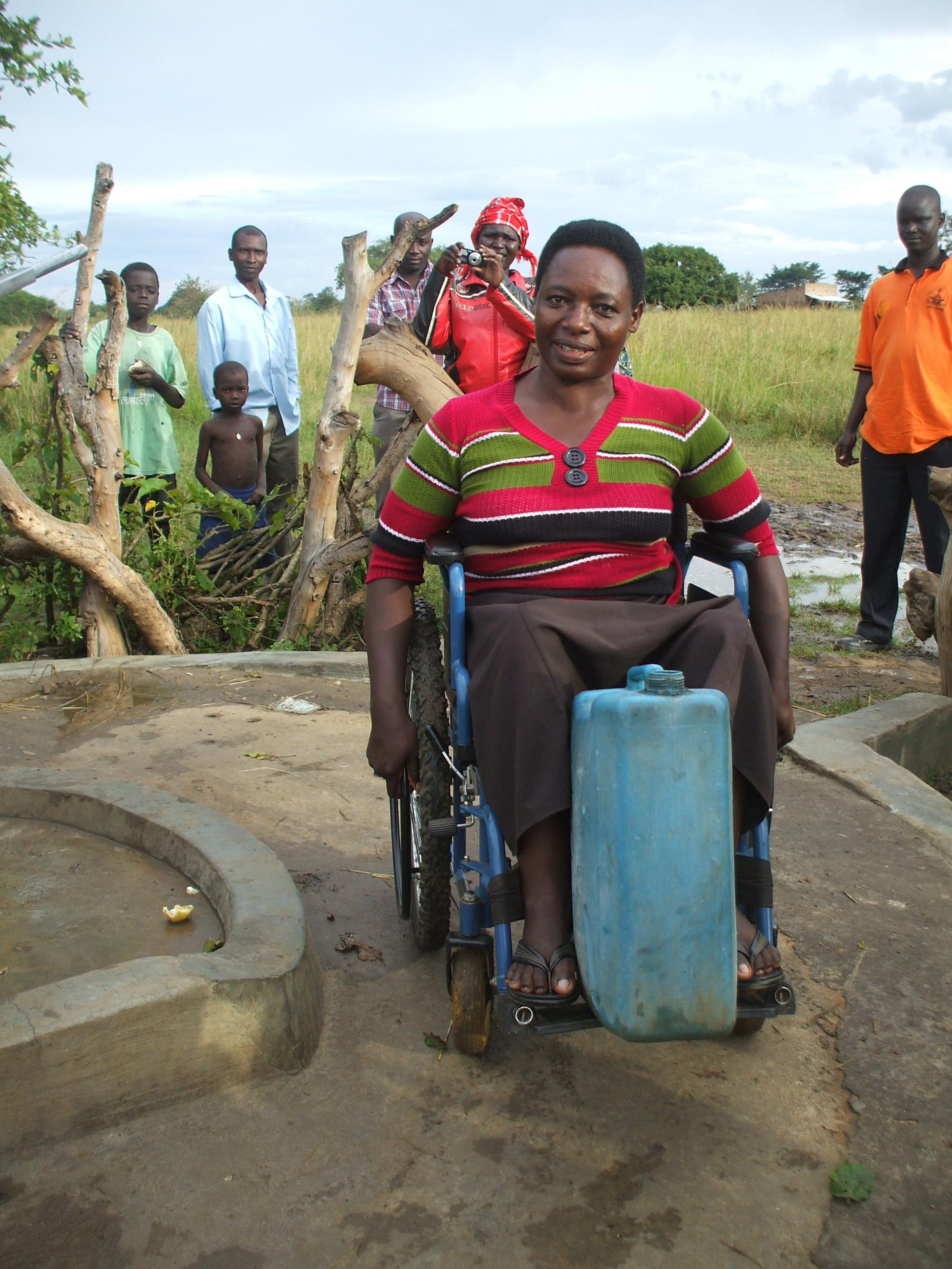 A woman using a wheelchair next to a well, with a water jerry can placed on her footholder.