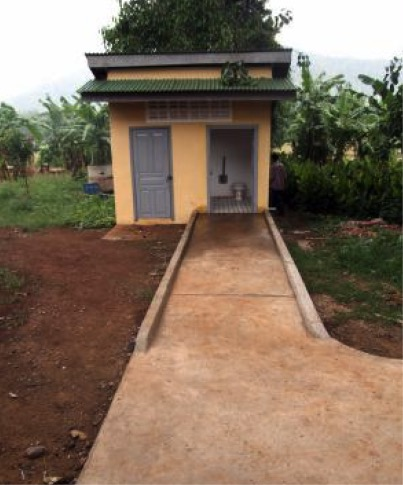 A wash room facility accessed by a path and ramp leading to the entrance