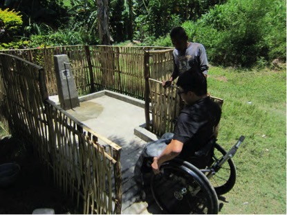 A man using a wheelchair is testing an accessible waterpump, by using the ramp up to the apron.