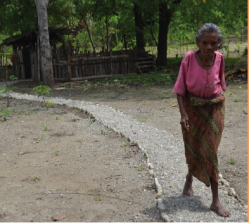 A woman walking on a marked path, signed off by small stones as guardstops and guidance
