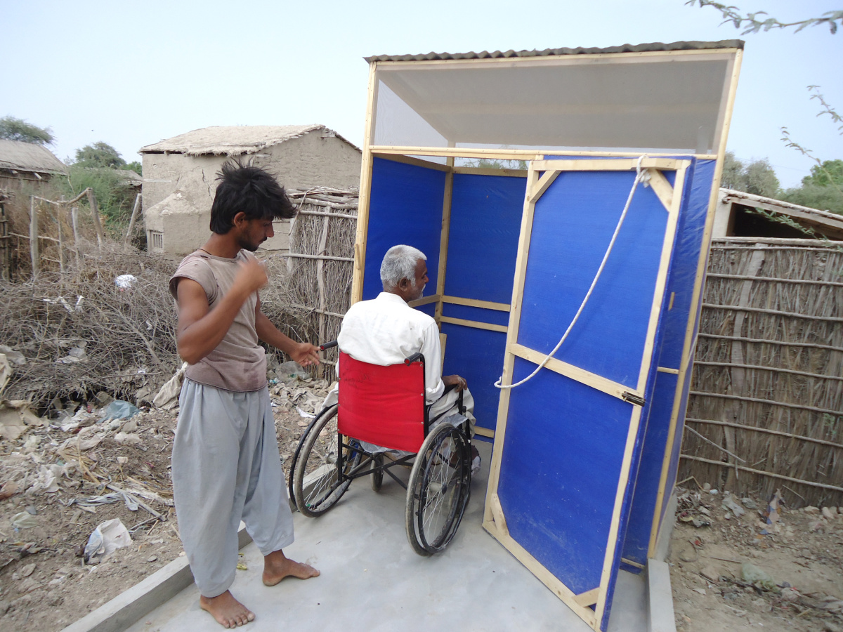 A man using a wheelchair is entering a latrine made from plastic tarps. The lartine is accessed by a ramp and the door has a lock function using a rope