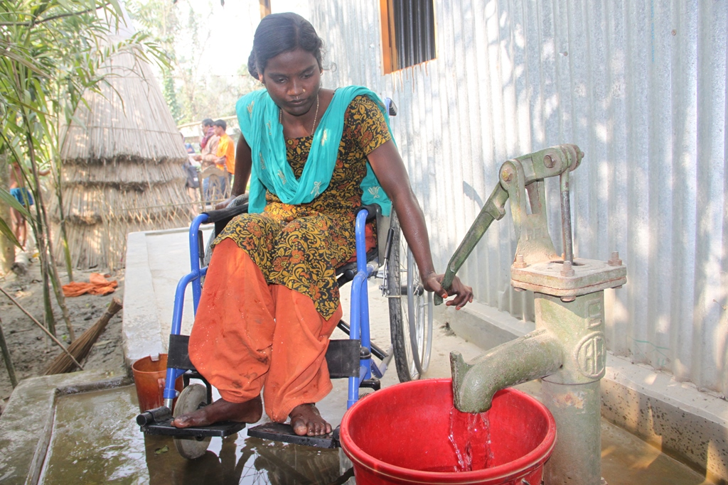 Women in a wheelchair in Bangladesh is using a hand pump to get water.